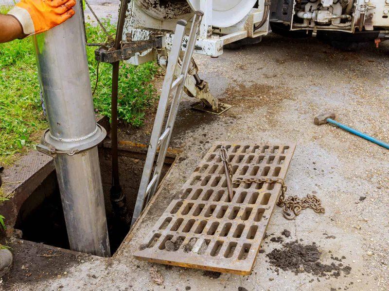 Le camion de nettoyage industriel des eaux usées nettoie l'obstruction d'une canalisation d'égout de l'intérieur.